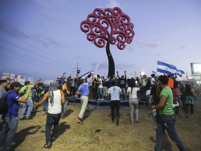 Anti-government protesters gather below the one metal tree sculpture remaining after pulling down a second one, a monument that is emblematic of the government of Nicaraguan President Daniel Ortega, at the Jean Paul Jennie round-about in Managua, Nicaragu