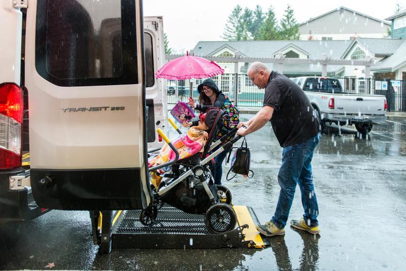 Dunn carefully loads Holt into the van as her mom, Meagan Holt, looks on.