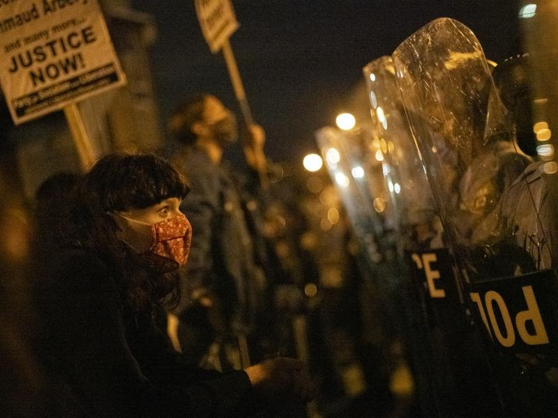 A demonstrator confronts police officers during a protest against the shooting of 27-year-old Walter Wallace.