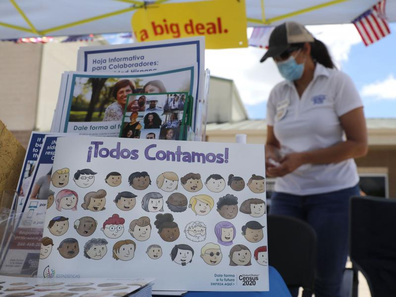 U.S. Census Bureau worker Marisela Gonzales stands by a display of books and flyers about the 2020 census at a walk-up counting site in Greenville, Texas, in July. The bureau's employees are under a time crunch to try to complete the national head count a