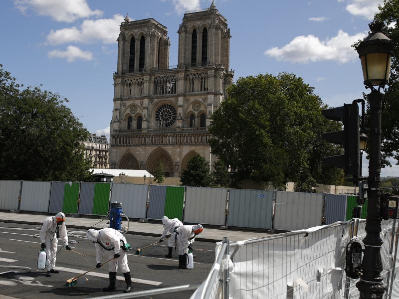 A cleanup crew scrubs pavement in front of the cathedral on Monday, after French inspectors said workers could return to the fire-damaged site to continue repairs.