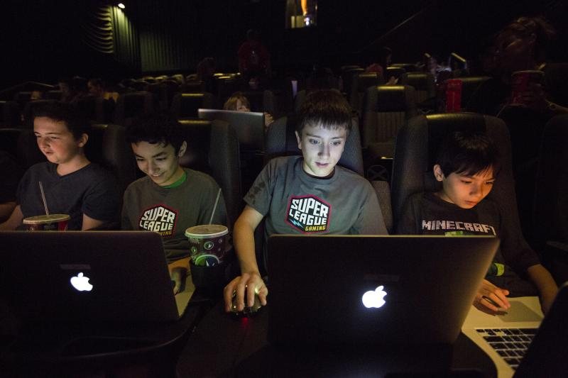Tyler Hines (from left), Jaden Bautista, Eric Apfelbaum, and Justin Bautista play Minecraft together for the Super League Gaming event at Regal Cinemas on Monday in New York City. The players were able to build their own creations in Minecraft and battle