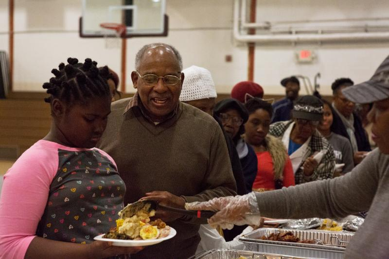 Harold Valentine (center), a local resident, attends a community Thanksgiving meal at Kennedy Recreation Center in Shaw.