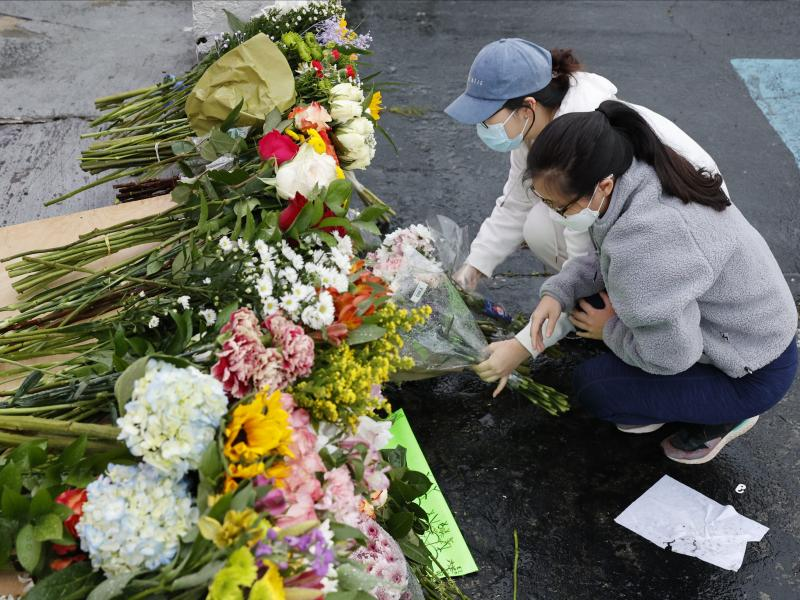Jenny Choi (left) and Kristi You place flowers Wednesday at the entrance of Gold Spa, one of three locations where deadly shootings happened in the Atlanta area this week.
