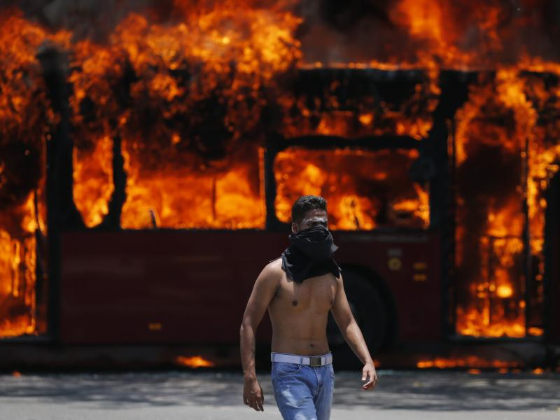 An anti-government protester walks near a bus that was set on fire by other protesters during clashes between rebel and loyalist soldiers in Caracas, Venezuela, on Tuesday.