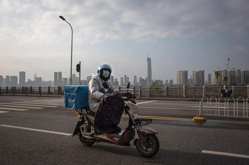 A delivery worker on a motorcycle on an empty street in Wuhan. Despite the city's lockdown measures to prevent the spread of disease, a handful of delivery companies are still in operation. Their workers provide supplies and necessities to residents coope