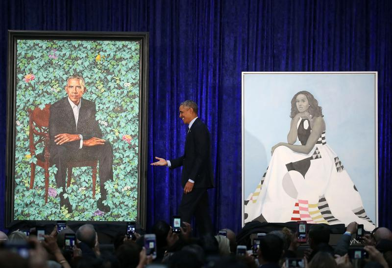 """Obama stands between the portraits. His will be permanently installed in the """"America's Presidents"""" exhibit at the National Portrait Gallery in Washington, D.C."""