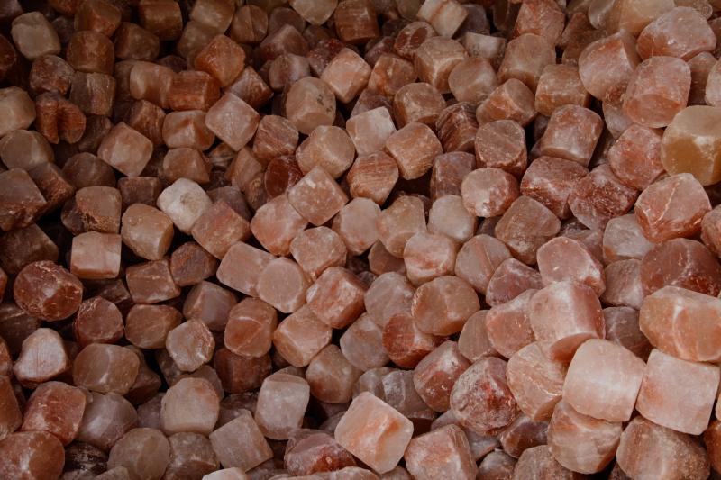 A pile of rough-hewn pink Himalayan salt cubes.