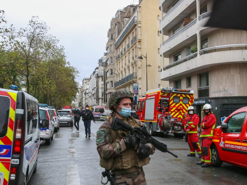 An officer of the French National Gendarmerie guards an area near the former Paris offices of satirical newspaper Charlie Hebdo, where two people were wounded Friday in an attack with a sharp object that one witness described as a hatchet.