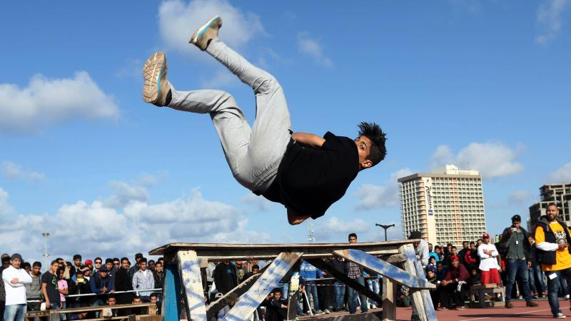 A Libyan youth displays his skills in parkour, an extreme sport, during a friendly competition in Tripoli on March 7, 2014.