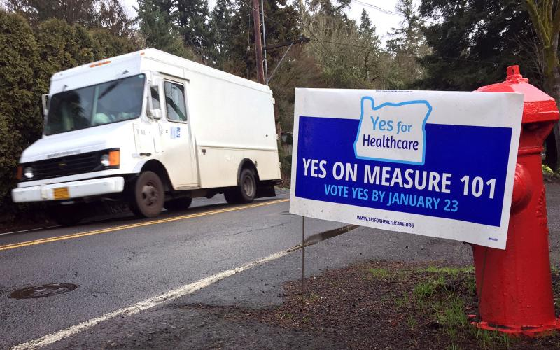 A sign in support of Oregon's Measure 101 is displayed by a homeowner along a roadside in Lake Oswego, Ore. Tuesday's special election puts decisions over how the state funds Medicaid in voters' hands.
