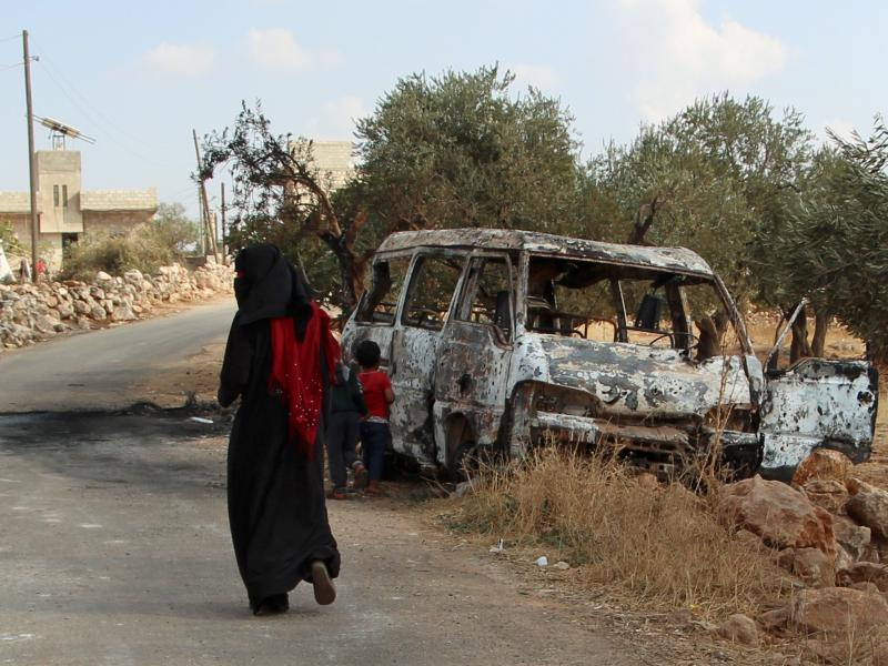 A woman walks past a wrecked van near the northwestern Syrian village of Barisha. Local residents and medical staff told NPR that noncombatant civilians who were in the van were injured and killed last year the night of the U.S. raid on the compound of IS