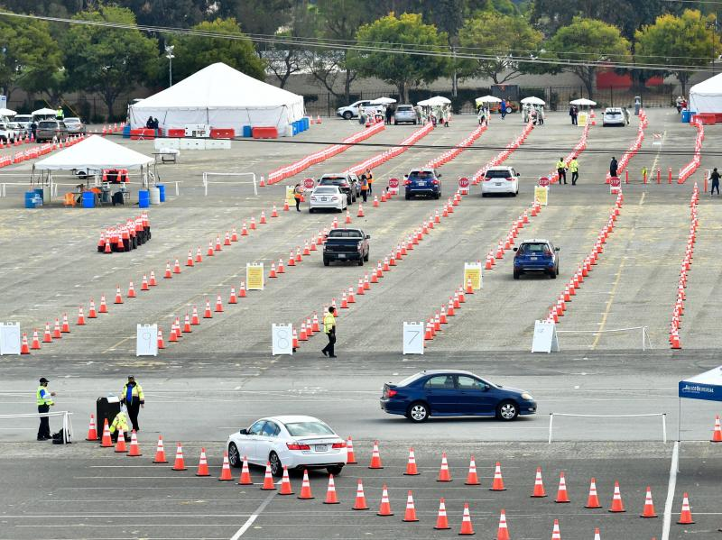 People wait for COVID-19 vaccinations in their vehicles at the Fairplex fairgrounds in Pomona, Calif., last month. The White House announced on Friday that active duty military personnel will soon be deployed to assist at vaccination sites, starting this