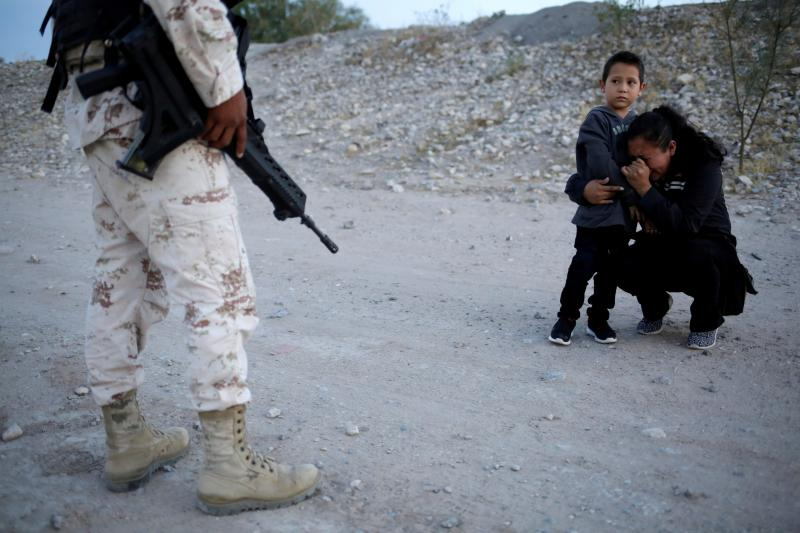 Guatemalan migrant Lety Pérez embraces her son, Anthony, while pleading with a Mexican National Guard member to let them cross into the United States, near Juárez, Mexico, on Monday.