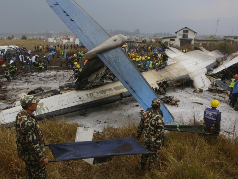 Nepalese rescuers work after a passenger plane from Bangladesh crashed at the airport in Kathmandu, Nepal, on Monday.