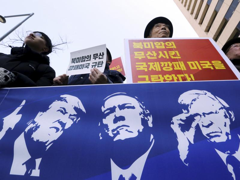 Protesters hold a banner showing images, of President Trump, Secretary of State Mike Pompeo, and National Security Adviser John Bolton during a rally against U.S. sanctions on North Korea, near the U.S. Embassy in Seoul, South Korea.