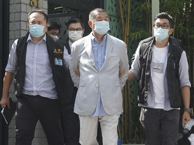Hong Kong media tycoon Jimmy Lai (center) is arrested at his home in Hong Kong on Monday. Hong Kong police raided the publisher's headquarters in the highest-profile use yet of the new national security law Beijing imposed on the city after protests last