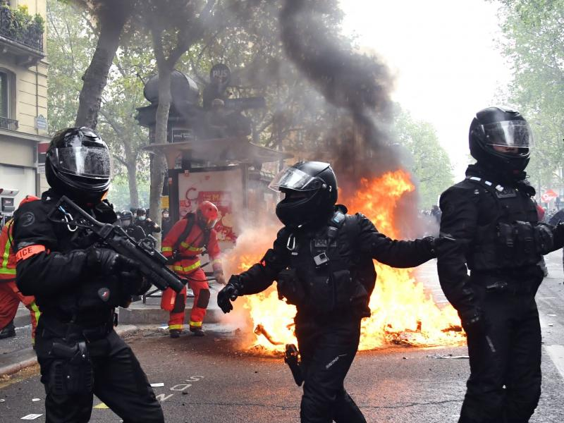 Police officers walk near a fire burning in the street during May Day protests in Paris on Saturday.