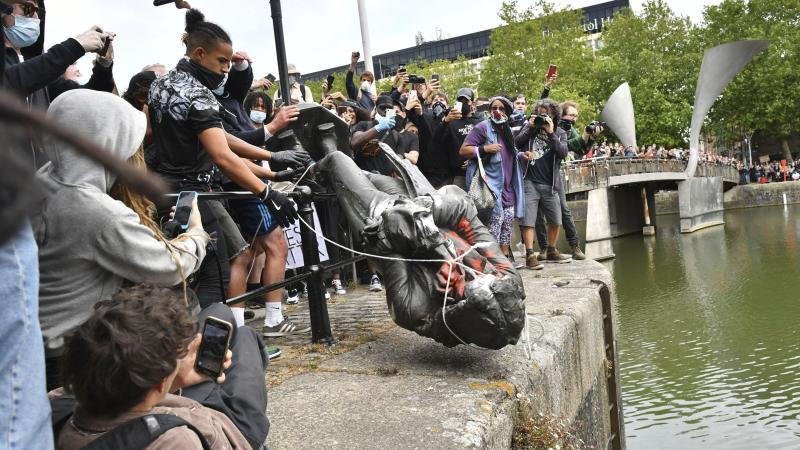 Protesters throw a statue of slave trader Edward Colston into Bristol Harbor on Sunday during a Black Lives Matter protest in England.