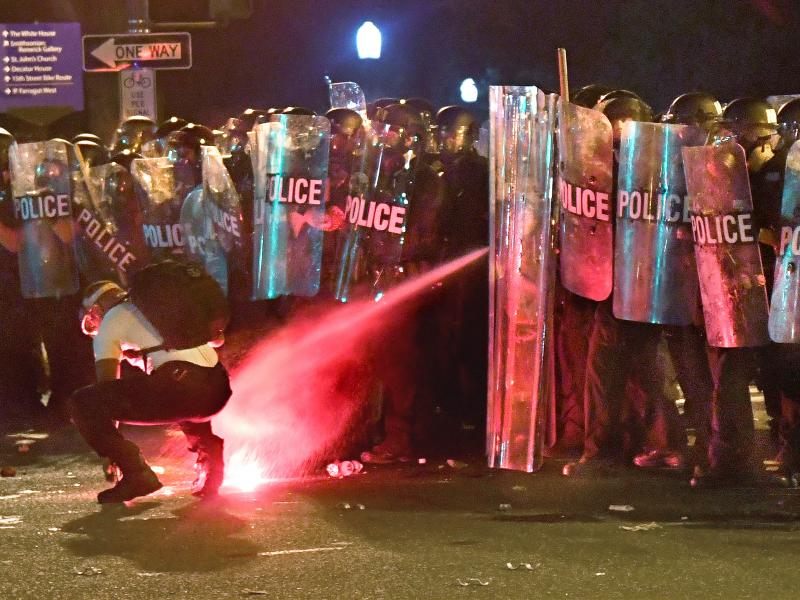 An anti-racism protester near Lafayette Square in Washington, D.C., in May is tear-gassed as he attempts to retrieve a flare thrown at police.