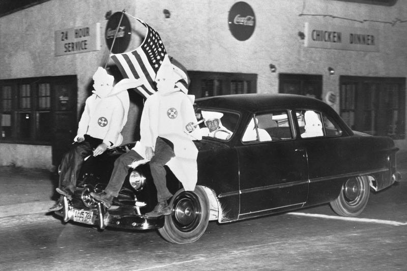 In 1949, Ku Klux Klan members ride down a street in Gadsden, Ala., as part of an 18-car parade.
