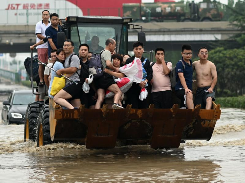 People ride in the front of a wheel loader to cross a flooded street following heavy rains which caused flooding and claimed the lives of at least 63 people in the city of Zhengzhou in China's Henan province on July 23.