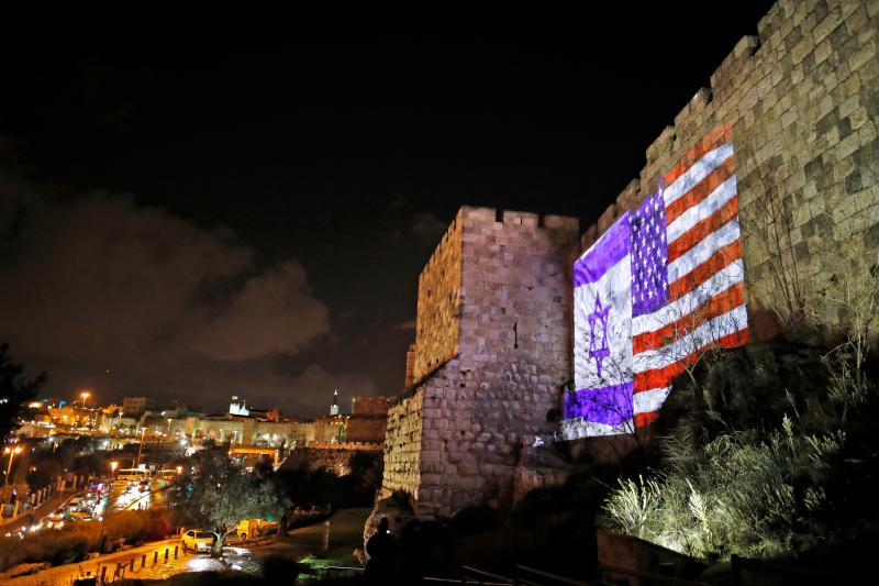"""The American and Israeli flags are on display Wednesday on the walls of the Old City of Jerusalem. President Trump announced that the U.S. will view Jerusalem as the capital of Israel, and he ordered the State Department to """"begin preparation to move the"""