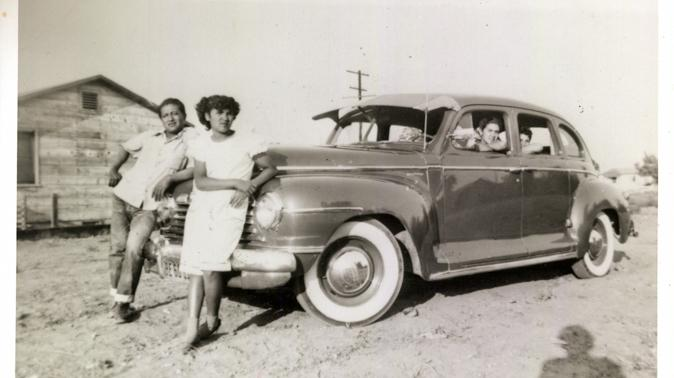 """Ricardo """"Papu"""" Ovilla, left, and the family's first car. Ovilla is pictured with his children Martha (next to him) and Aurelia and Rodolfo Sandoval (left to right, inside the car) in a photo taken in 1949 at a labor camp in Escondido, Calif."""