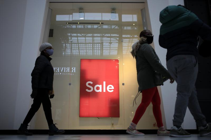 "Shoppers walk past a ""Sale"" sign outside a store at the Easton Town Center Mall in Columbus, Ohio, on Jan. 7."