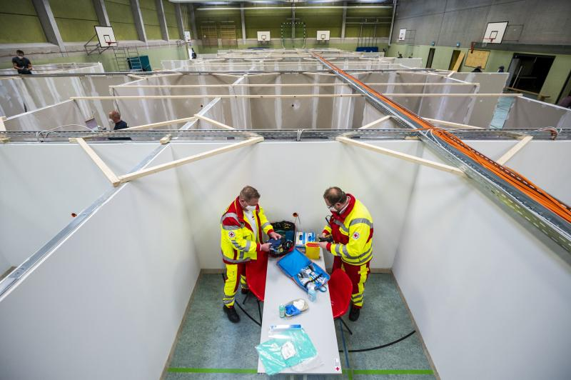 """The pending arrival of vaccines has brought """"hope for a brighter future,"""" the OECD says. Here, workers from the Red Cross and the Federal Agency for Technical Relief help set up a center for COVID-19 vaccinations in a gymnasium in Eschwege, Germany."""