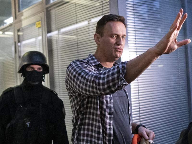 Russian opposition leader Alexei Navalny gestures while speaking to the media as a security officer guards an entrance of the Anti-Corruption Foundation office in Moscow, Russia, Thursday. The federal court bailiffs' service that conducted the Thursday ra