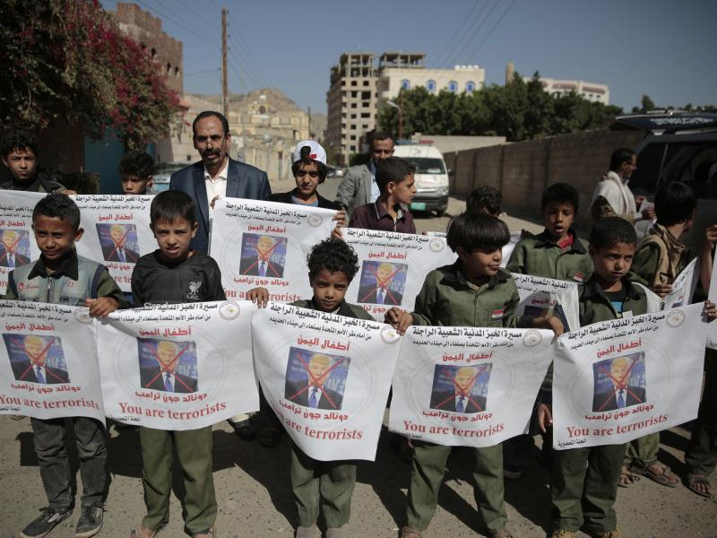Boys hold posters with crossed-out pictures of President Trump during an April march against plans by the Arab coalition to attack Hodeidah, Yemen.