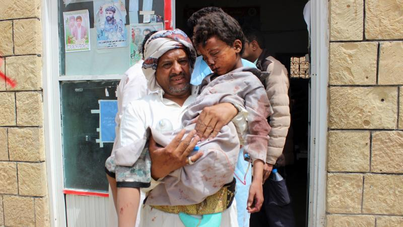 A man carries a wounded child to the hospital Thursday after the Saudi-led coalition carried out an airstrike on a crowded area in Houthi-controlled Saada province. At least 29 children under the age of 15 were killed in the attack, according to the Inter