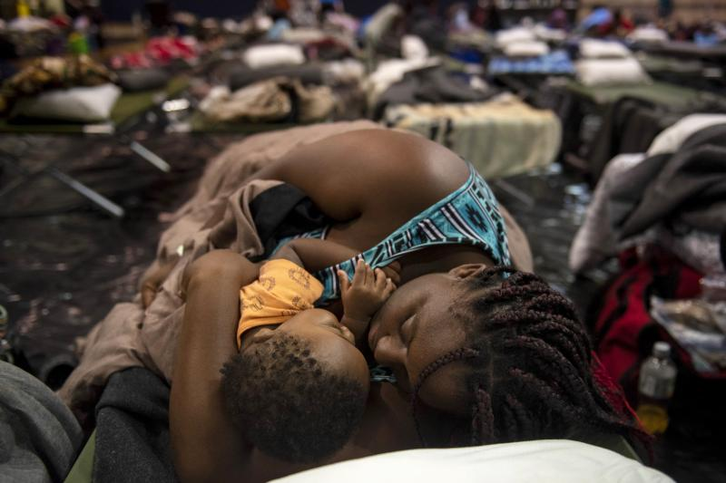 A woman holding a child sleeps after being evacuated at Southeast Raleigh High School ahead of Hurricane Florence in Raleigh, N.C. on Wednesday.