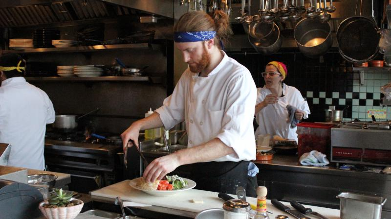 Carter Jorgensen, with head chef Zephyr Paquette in the background, at Seattle's Coastal Kitchen. Restaurants are one of the largest employers of low-wage workers in the city.