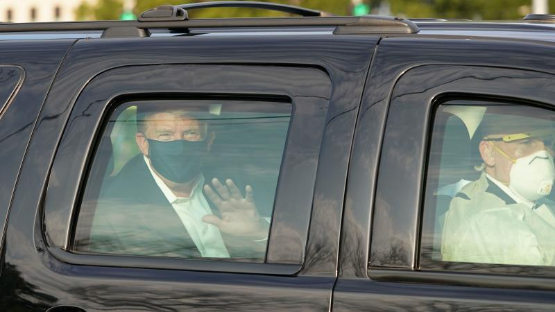President Trump waves from a motorcade outside Walter Reed Medical Center, accompanied by Secret Service agents on Sunday.