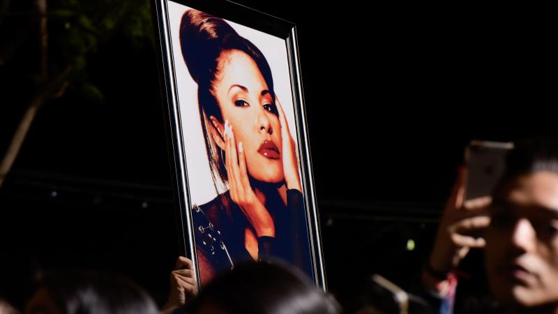 Fans with a photo of Selena during a ceremony honoring her in 2017. Over the decades since her death, Selena's legacy has become even more profound than writer Deborah Paredez ever anticipated.