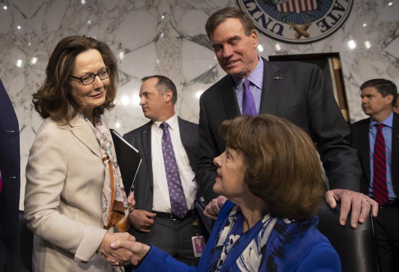 Gina Haspel (in white), the nominee to lead the CIA, is welcomed at her confirmation hearing before the Senate intelligence committee by Sen. Dianne Feinstein, D-Calif. (seated), and Vice Chairman Mark Warner, D-Va., in Washington on May 9. The committee