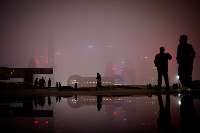 People walk on the Bund, the riverfront area next to the financial district in Shanghai. Many foreigners have descended on Shanghai to make money on China's economic expansion. NPR's Frank Langfitt met one such woman as part of the free taxi rides he's be