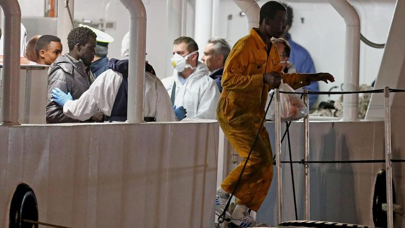 Italian authorities aboard the Italian coast guard vessel Bruno Gregoretti check on migrants who survived a recent sinking in the Mediterranean Sea. The coast guard vessel arrived at Catania's port in Sicily on Tuesday.