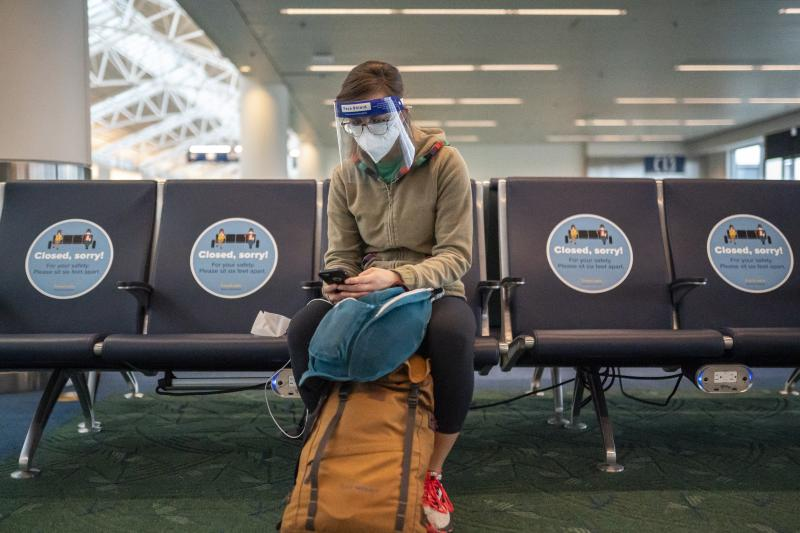 A traveler waits for a flight at Portland International Airport in Oregon last week. Public health experts say it's important that people who traveled or gathered with others are especially careful over the next two weeks.