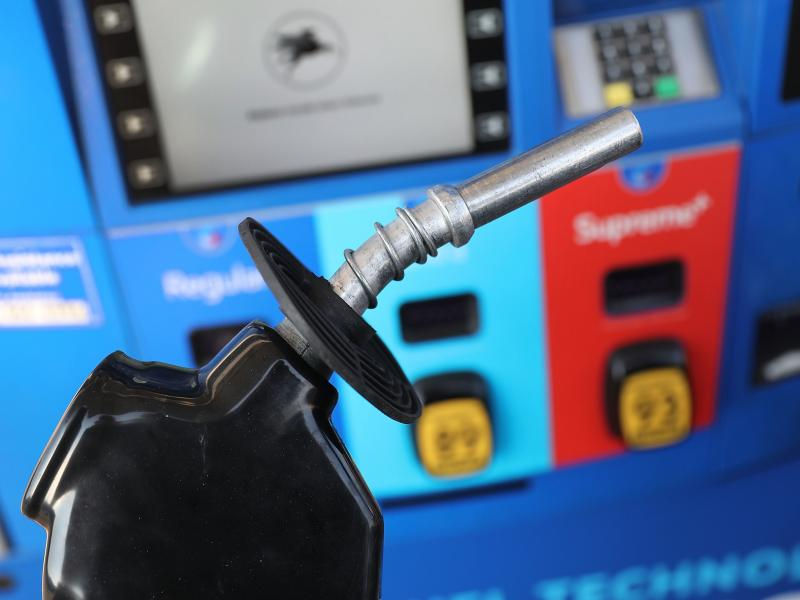 A gas pump nozzle is seen at a Miami gas station in 2018. Some activist shareholders are pushing companies to tie executive compensation to meeting climate targets.