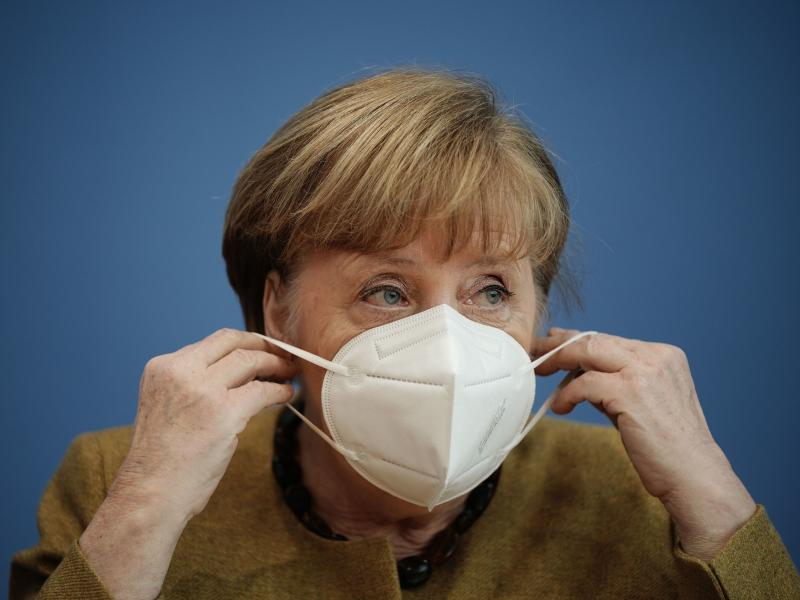 German Chancellor Angela Merkel puts on her face mask after a news conference in Berlin last week. Germany has introduced new requirements for medical-grade masks to be worn on public transit and in shops.