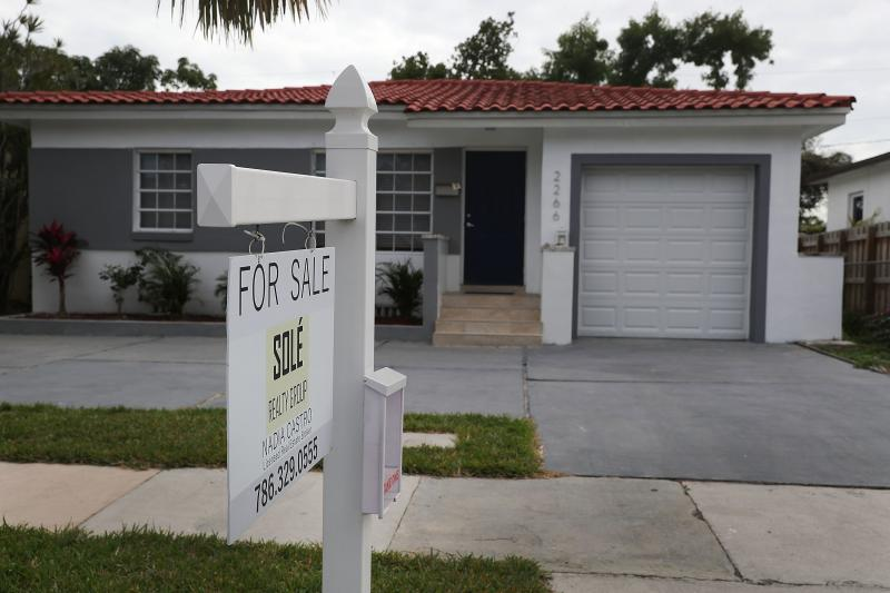 """A """"for sale"""" sign is seen in front of a home in Miami on Jan. 24, 2018. The partial shutdown of the federal government is causing some financial problems for furloughed workers who can't refinance their mortgages or buy homes because lenders can't verify"""