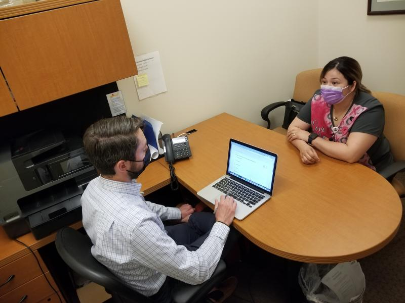 Attorney Marc Scanlon meets with client Kimberly Ledezma at Salud Family Health Centers' clinic in Commerce City, Colo. Every day in this Denver suburb, four lawyers join the clinic's physicians, psychiatrists and social workers to consult on cases, as pa