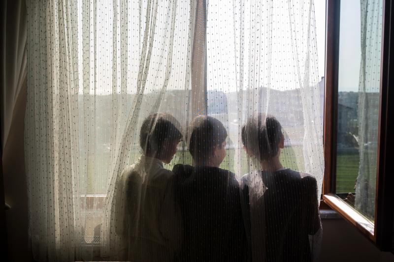 Ten-year-old Nurzat (right) and his friends, brothers Abdulla (left), 11, and Muhammet (center), 10, look out the window of their dormitory room at a boarding school in Istanbul, Turkey. The boys are all missing their parents, who are believed to be in pr