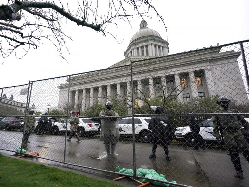 Members of the Washington National Guard stand near a fence surrounding the Capitol in Olympia, Wash., in anticipation of protests on Jan. 11, 2021.