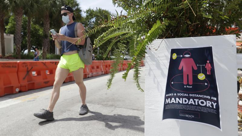 A pedestrian in a mask passes a sign urging people to practice social distancing, on Saturday in Miami Beach, Fla. Just as residents flocked outside to enjoy the Fourth of July, states such as Florida were reporting skyrocketing numbers of confirmed coron