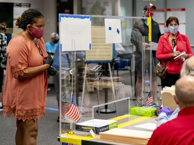 A voter stands by for her ballot as people wait more than four hours for early voting Friday in Fairfax, Va.