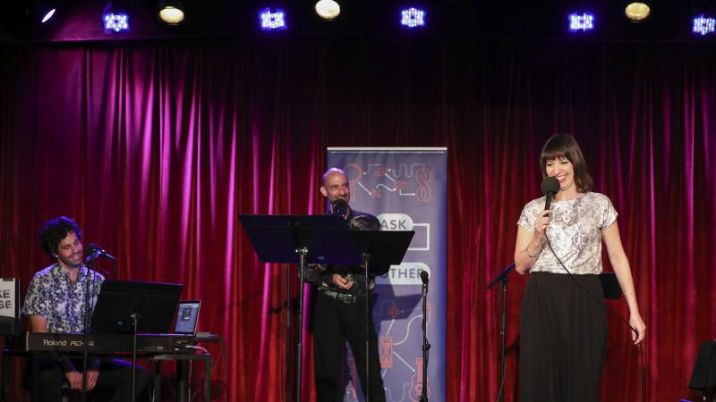 Ask Me Another host Ophira Eisenberg performs on stage alongside guest musician Julian Velard and guest announcer Cecil Baldwin at the Bell House in Brooklyn, New York.